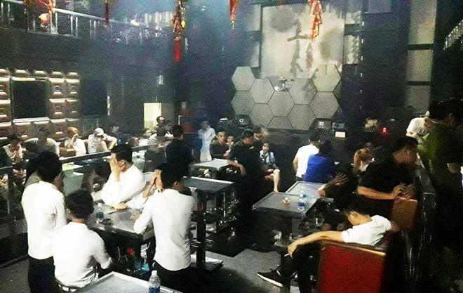 Khách chơi ở quán bar bị lực lượng chức năng bắt ngồi tại chỗ để kiểm tra hành chính. Ảnh: H.Đ.