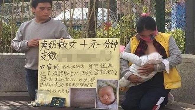 Người mẹ trẻ cùng chồng quỳ trên vỉa hè để bán sữa kiếm tiền chữa bệnh cho con.
