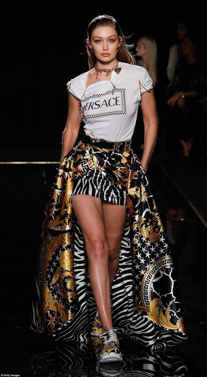 Gigi Hadid xuất hiện với bộ cánh phá cách, chân váy phối họa tiết nổi bật. Tô điểm cho chiếc áo thun là những chiếc kim băng đặc trưng của thương hiệu, được ghim xung quanh áo.