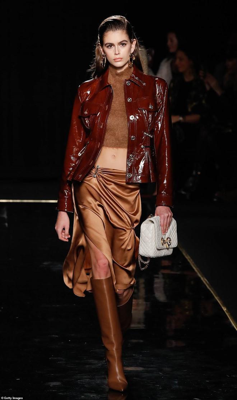 Kaia Gerber là gương mặt quen thuộc trong suốt các show thời trang lớn của các nhãn hàng. Cô diện thiết kế màu nâu da bò phối với áo khoác da bóng nhựa màu đỏ đất cực kì cá tính trên sàn catwalk.