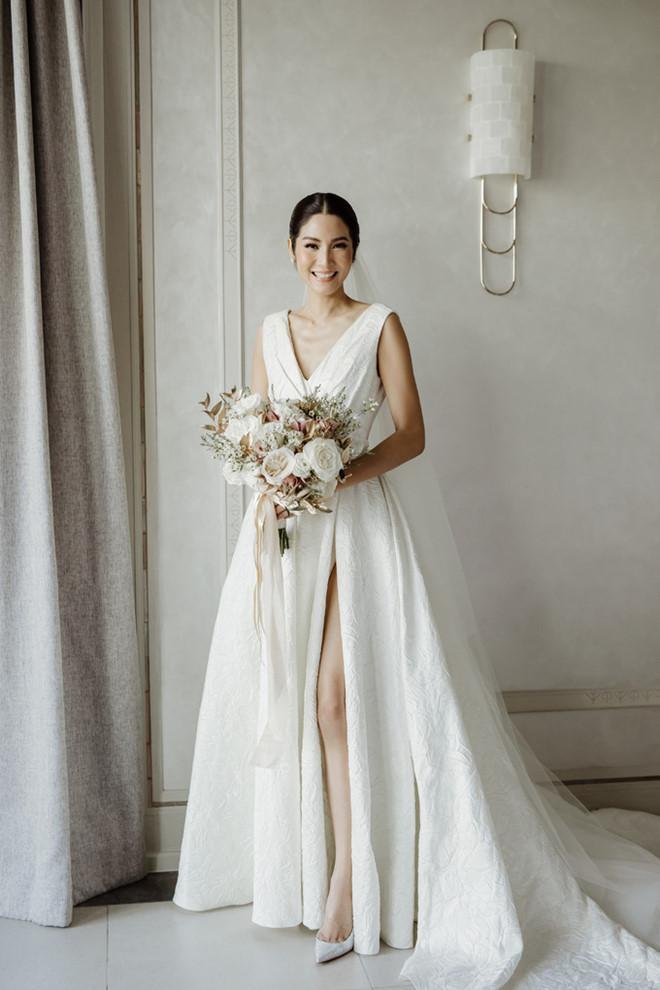 Trong ngày cưới, Hoa hậu Hoàn Vũ Thái Lan Farung Yuthithum chọn diện thiết kế của Đỗ Mạnh Cường. Người đẹp 31 tuổi diện chiếc váy xoè dài với phần ngực xẻ chừng mực, có những nếp gấp tạo phom ở hai bên.