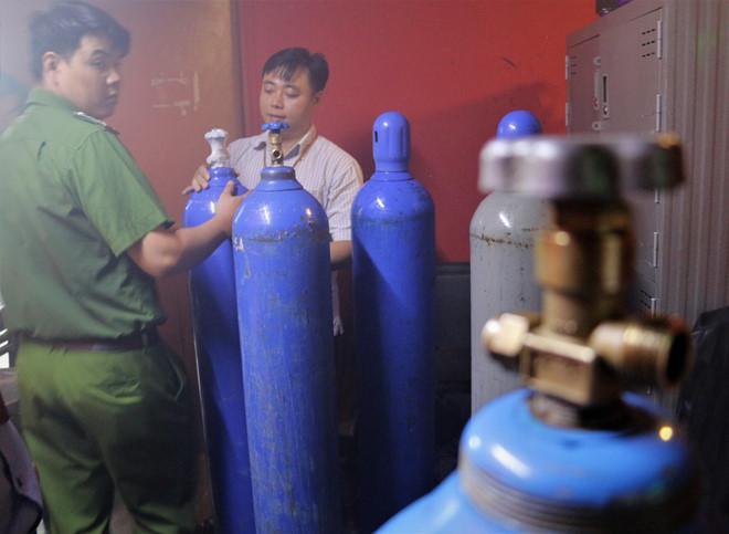 Lực lượng chức năng thu giữ 14 bình khí dùng bơm bóng cười tại nhiều cơ sở kinh doanh ở phố Tây Bùi Viện. Ảnh: Trần Anh.