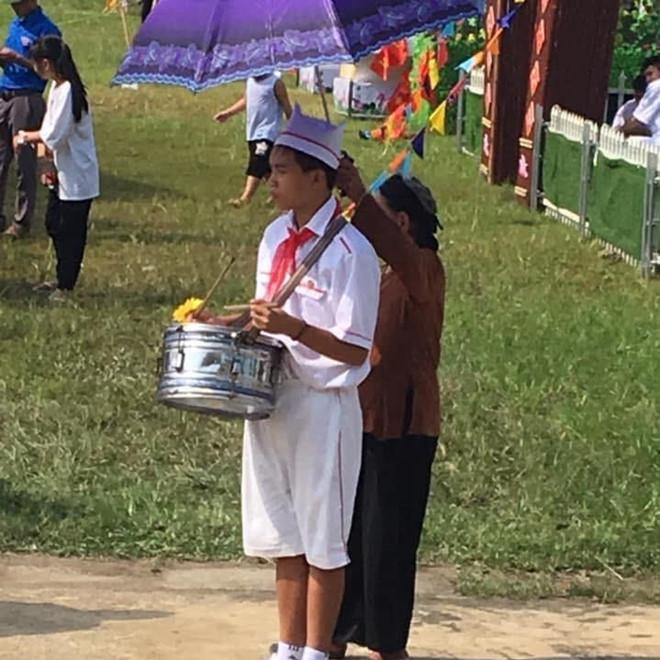 Người bà thấp hơn cháu rất nhiều, nhưng vẫn cố sức rướn tay để giữ chiếc ô.