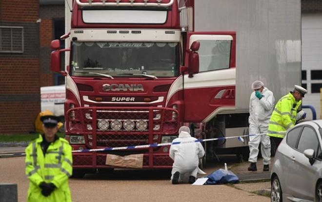 Nhân viên pháp y và cảnh sát đang khám nghiệm xe container chứa 39 thi thể người.