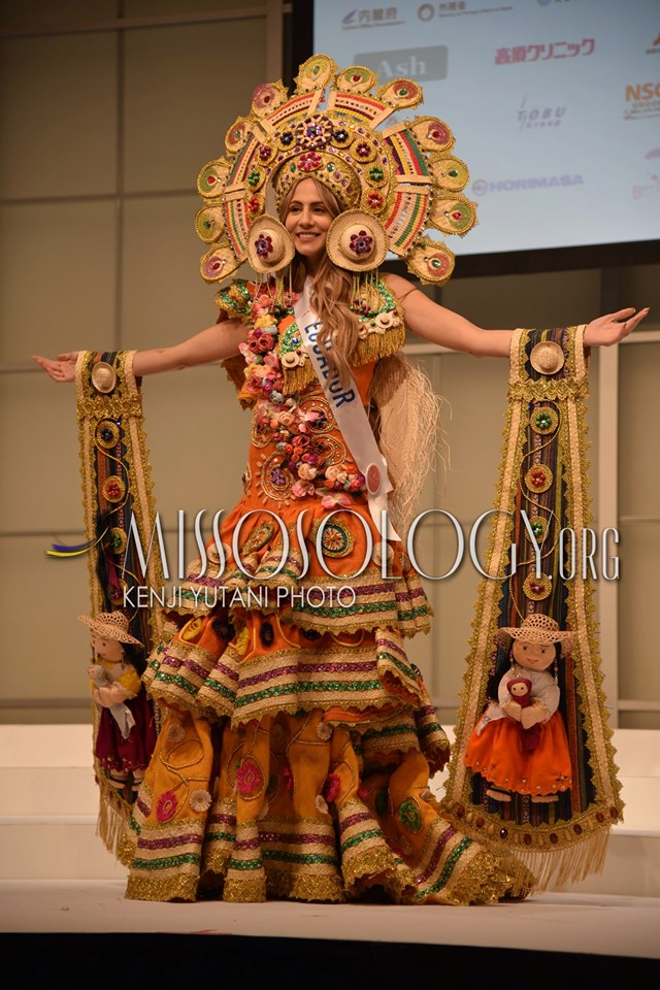 Hoa hậu Ecuador mang một thiết kế cầu kì với những chú búp bê, vòng hoa, vải gấm sặc sỡ sắc màu. Đây cũng là những vật phẩm quen thuộc của người Ecuador trong các lễ hội truyền thống.