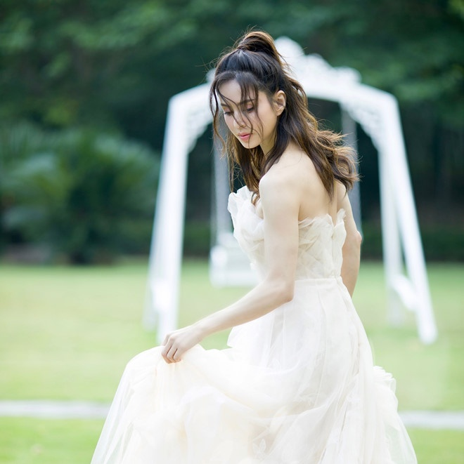 """Trong kiểu váy cưới trắng bung xòe, khán giả đã để lại nhiều bình luận khen ngợi cô:"""" Bao nhiêu năm vẫn là Tiểu Long Nữ đẹp nhất"""" . Nhan sắc của cô luôn là đề tài nóng trên các trang xã hội"""