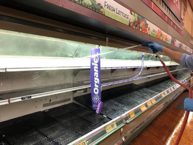 Các nhân viên cửa hàng nhanh chóng khử khuẩn các kệ hàng để bày bán thực phẩm trở lại.