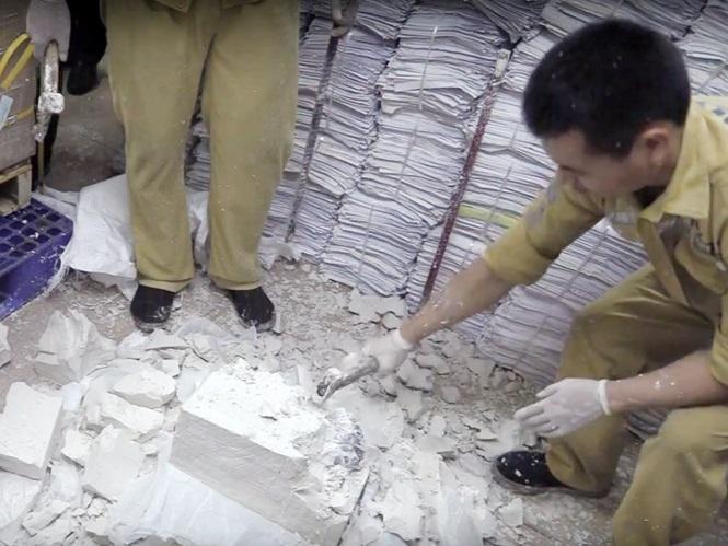 Lực lượng chức năng đục khối thạch cao để lấy sừng tê giác bên trong. Ảnh: Tiền Phong