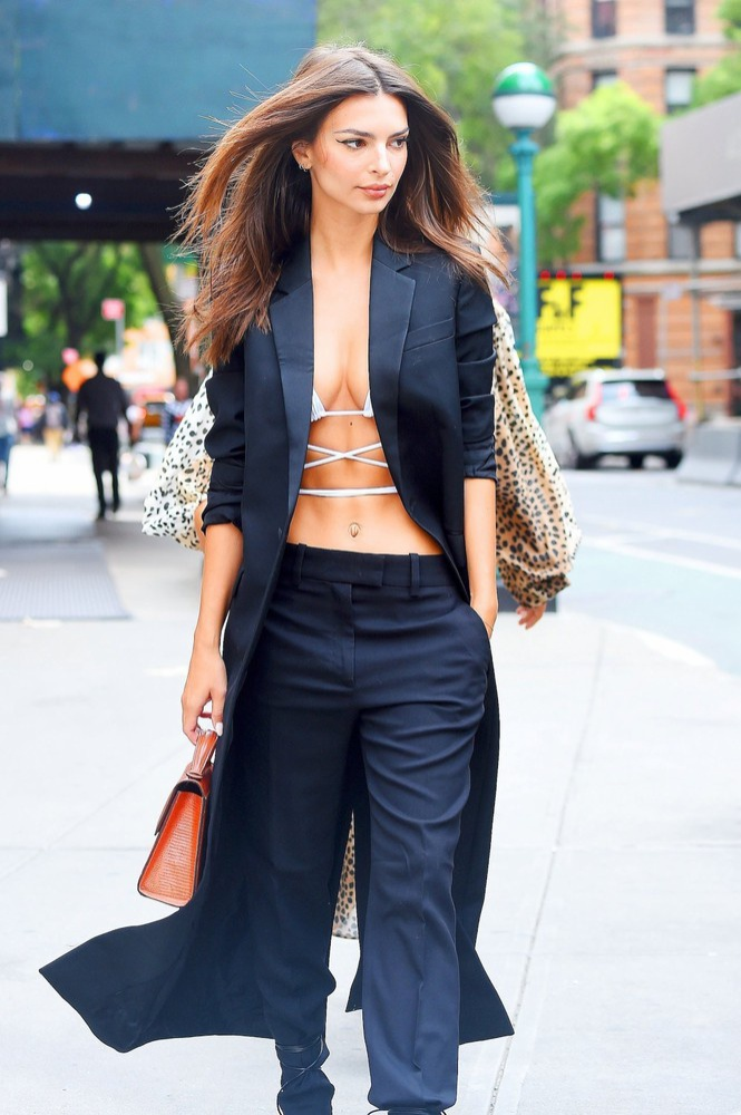 Chân dài chọn bô suit với kiểu áo khoác dáng dài mix cùng quần tây ôm, bên trong là áo bikini đan xen dây màu trắng gợi cảm, phụ kiện là túi xách hình hộp chữ nhật tinh tế