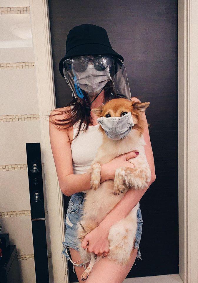 Không riêng gì bản thân trang bị khẩu trang và mũ che kín mít mà Khánh Vân còn cho chú chó cưng của mình mang khẩu trang.