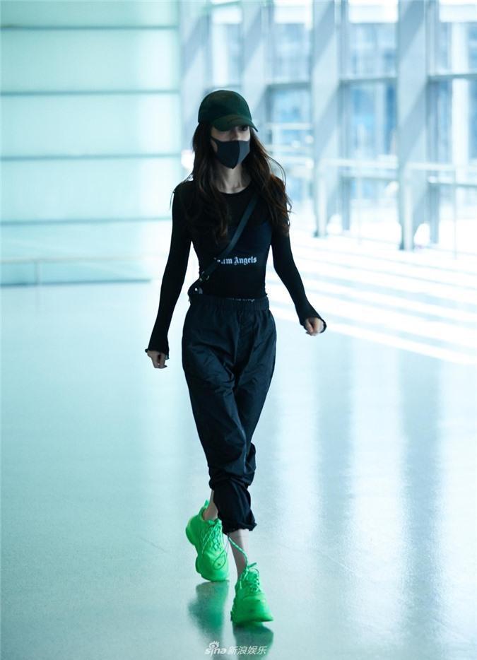 Angelababy diện bộ đồ màu đen cá tính cùng đôi giày thể thao xanh chuối kết hợp mũ lưỡi trai tại sân bay