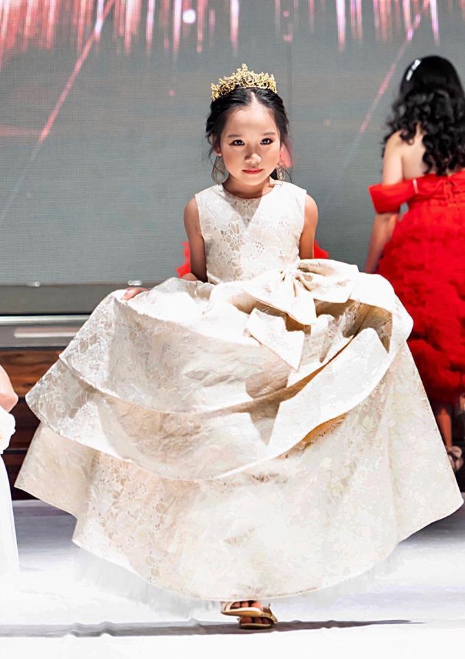 Chiếc váy xòe bềnh bồng nhiều lớp cùng vương miện đem lại nét đáng yêu, xinh xắn cho các mẫu nhí.