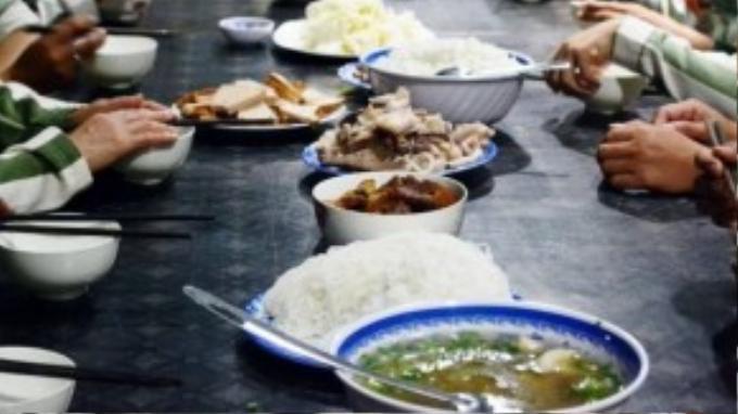 Trên bàn ăn gồm các món rau xanh, thịt kho, chân giò hầm, chả lụa…