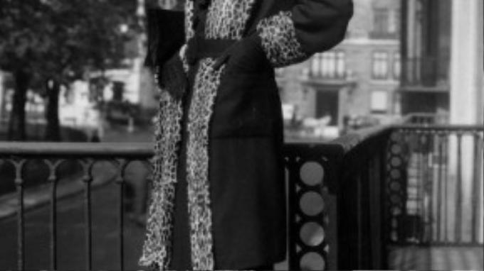Một người mẫu thập niên 30 tạo dáng thời thượng với họa tiết da báo được in chạy dọc chiếc áo choàng dáng dài.