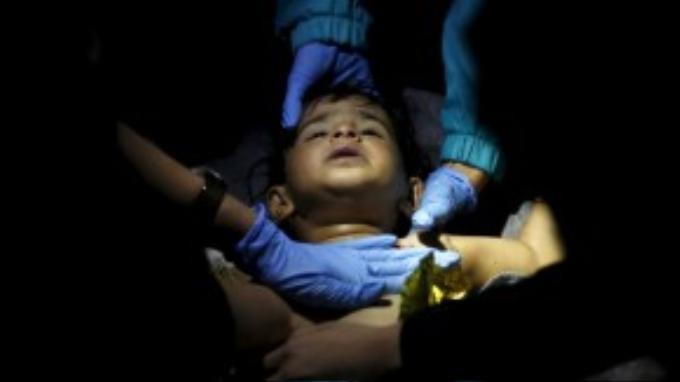 Các bác sỹ và tình nguyện viên sơ cứu một em bé bị đuối nước sau khi chiếc thuyền chở hàng trăm người tị nạn bị chìm trên đường đến Lesbos.