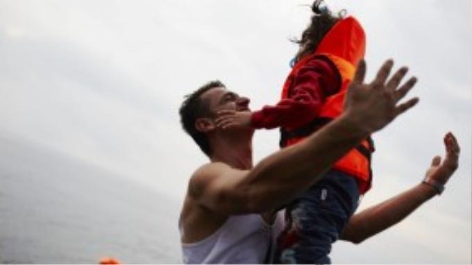 Một người cha vui mừng tung đứa con lên không ăn mừng việc cập bến an toàn tại Lesbos.