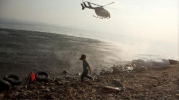 Một chiếc máy bay tuần tra trên bãi biển Lebos nơi một cậu bé người Syria vừa đặt chân lên đất Hy Lạp. Từ đây những người tị nạn sẽ tiếp tục hành trình di cư vào sâu lục địa già Châu Âu.