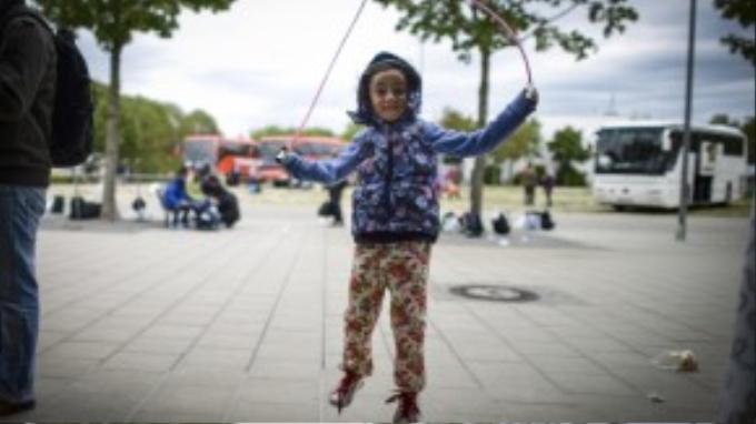 Cô bé Dima 5 tuổi đang nhảy dây trong một trại tị nạn ở Munich, Đức.