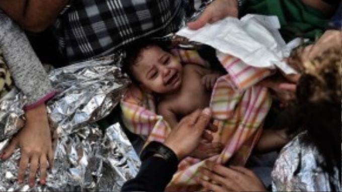 Một bé gái được cứu sống trong vòng tay những người tị nạn.
