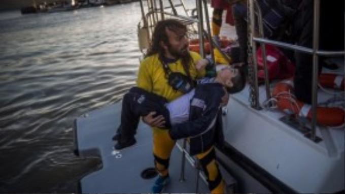 Nhân viên cứu hộ ôm xác một thiếu niên bị chết đuối sau vụ đắm thuyền. Có hàng trăm người đã chết hoặc mất tích dưới lòng biển sâu trên đường đến với vùng đất tương lai.