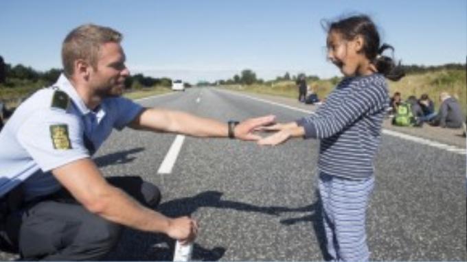 Một cảnh sát Đan Mạch vui đùa với một em bé Syria trên đường cao tốc gần Padborg.