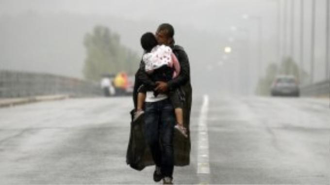 Ông bố Syria ôm hôn động viên đứa con khi bước đi dưới màn mưa lạnh, tiến về phía biên giới Hy Lạp – Macedonia.