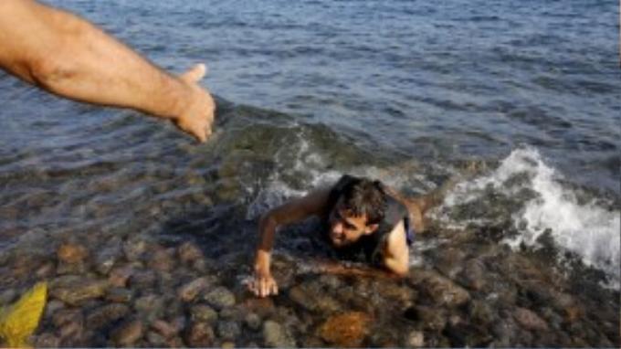 Bàn tay của tình nguyện viên đưa ra để kéo một người đàn ông bơi vào bờ biển sau khi chiếc thuyền chở người tị nạn như anh bị đắm.