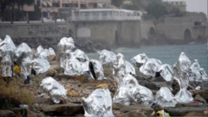 Một nhóm người tị nạn trùm những tấm chăn cứu thương khi bò qua biên giới Saint Ludovic ở biển Địa Trung Hải.