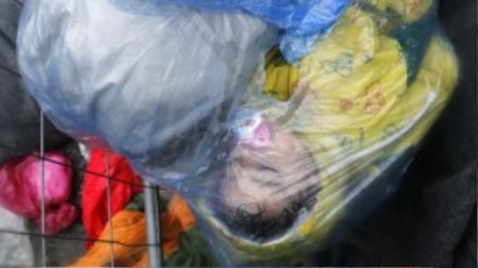 Một bé gái còn ngậm ti giả nằm ngủ trong chiếc áo mưa gần biên giới Slovenia – Croatia.