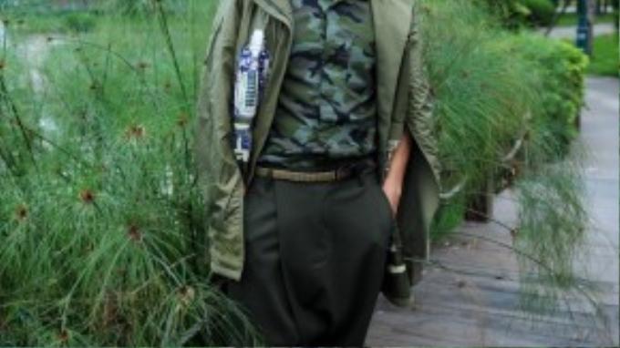 """NTK Trương Thanh Long tiếp tục lăng xê xu hướng military quân đội sau dư âm từ sự kiện chiếc áo do anh thiết kế được nữ ca sĩ Alicia Keys chọn mặc. Nếu Trương Thanh Long ở đêm đầu tiên của VDFW là một hình ảnh lịch lãm, bảnh bao thì đến ngày cuối cùng, anh lại """"nghịch ngợm"""", phá cách với gam màu olive trên chiếc quần đũng thụng cá tính."""