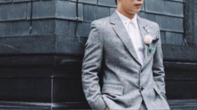 Xám luôn là màu được ưa thích mỗi độ Thu-Đông nhưng tông màu trung tính này cũng dễ khiến làm người ta lu mờ giữa những ngày u ám. Ý thức được điều đó, Travis Nguyễn tạo điểm nhấn nổi bật cho bộ vest với bông hoa giả màu hồng phớt xinh xắn ngay trước ngực.