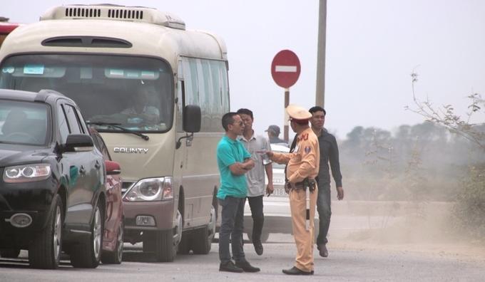 Một số lái xe đứng tán chuyện với cảnh sát giao thông trong lúc chờ phà.