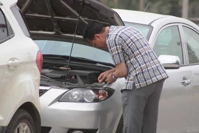 Người đàn ông tỉ mỉ vệ sinh máy xe để giết thời gian trong lúc chờ đợi. Người thân của anh đã chọn phương án chuyển sang đi tàu cao tốc ra Cát Bà.