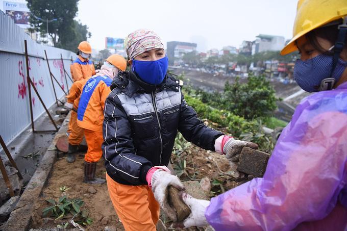 Ngay sau khi di dời cây xanh, công nhân Công ty Công trình giao thông Hà Nội khẩn trương bóc từng viên gạch vỉa hè đem về kho.