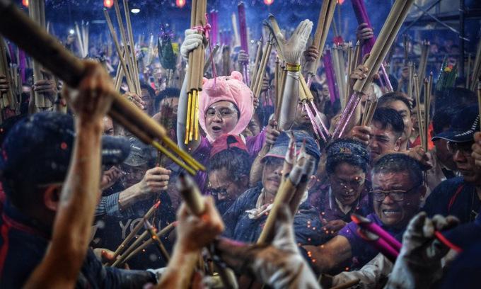 Hàng nghìn người dân Singapore hôm qua đổ tới chùa Kwan Im Thong Hood Cho để thắp hương cầu may mắn trong năm Kỷ Hợi. Một trong các nghi lễ được trông đợi vào đêm giao thừa chính là cuộc chạy đua trở thành người đầu tiên cắm cây hương vào lư hương trong chùa, theo Straits Times.Trong ảnh, những người tới chùa đang chen lấn để cắm cây hương.