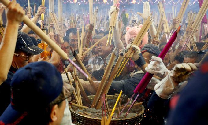 Những cây hương lớn được cắm vào lư ở giữa chùa Kwan Im Thong Hood Cho. Tục lệ này có ý nghĩa cầu may, người đầu tiên cắm hương được cho là sẽ được thần linh phù hộ trong năm mới.