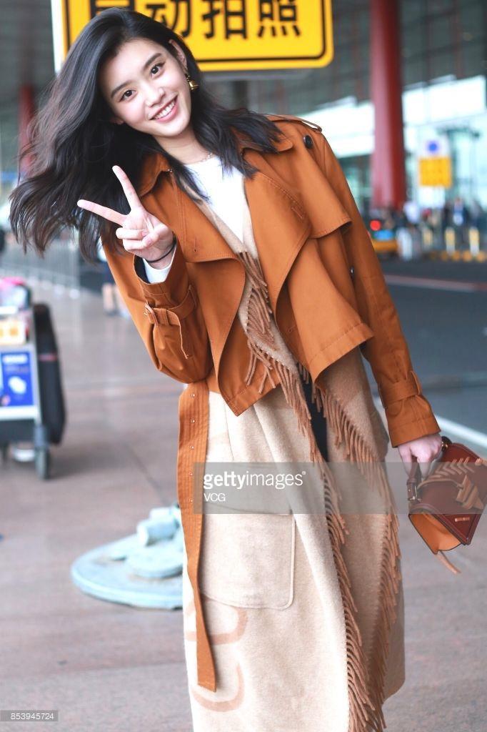Chiếc áo khoác của cô với chi tiết tua rua và gam màu cam đất tông xuyệt tông với chiếc túi xách nhỏ