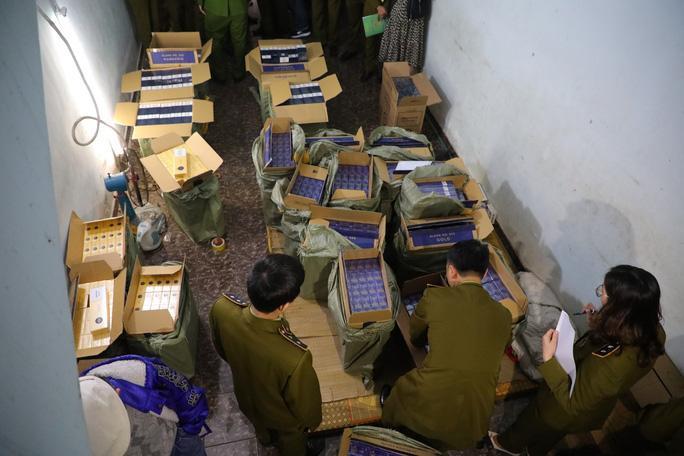 Lực lượng chức năng khám xét căn nhà chứa hàng ngàn gói thuốc lá lậu. Ảnh: báo Người Lao Động