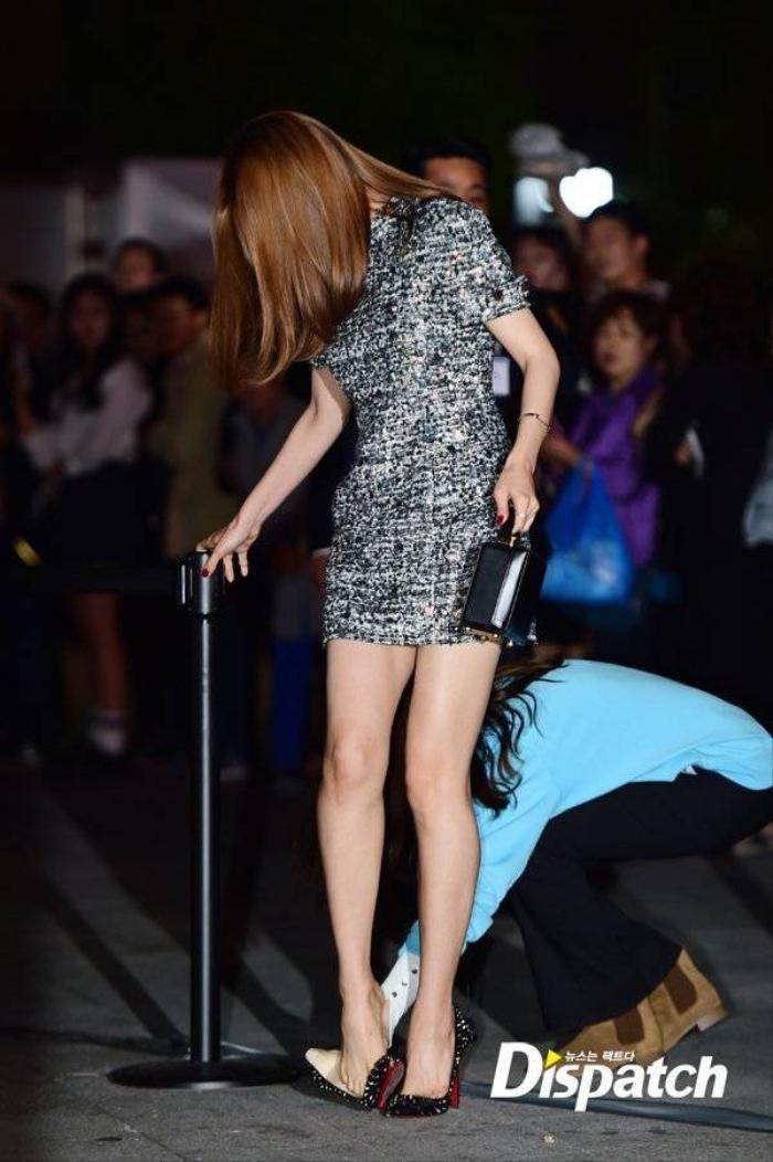 Một nhân viên trong ê-kíp nhanh chóng đến giúp nữ ca sĩ xỏ lại giày. Trước con mắt của nhiều người xung quanh, Son Na Eun ôm miệng cười ngượng ngùng.