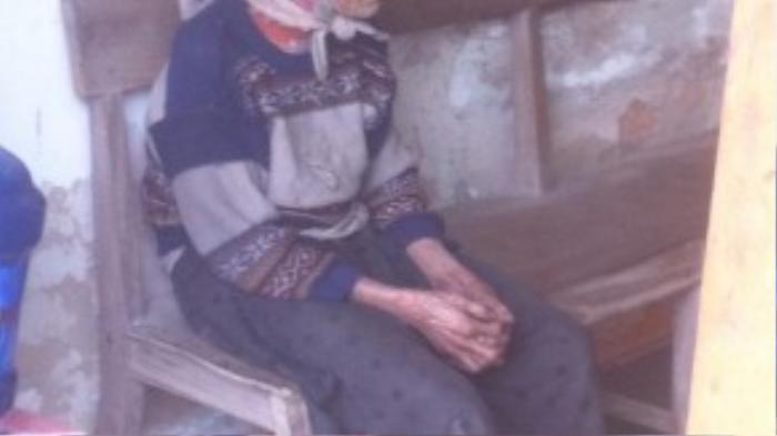 Cụ Lộc ngồi trong trụ sở của chính quyền thôn, trong lúc anh Minh nói chuyện xác minh gia cảnh cụ với cán bộ. (Ảnh: Phạm Ngọc Chiến)
