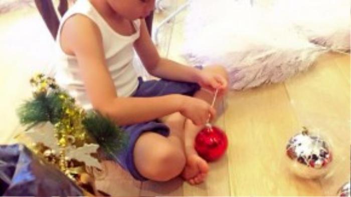 Con trai Hồ Ngọc Hà phụ mẹ cột dây vào trái châu nhiều màu sắc để chuẩn bị khâu trang trí cây thông.
