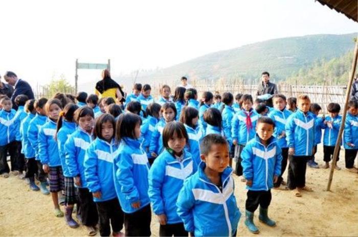 Trẻ em Mù Cang Chải xếp hàng nhận áo ấm cứu trợ.