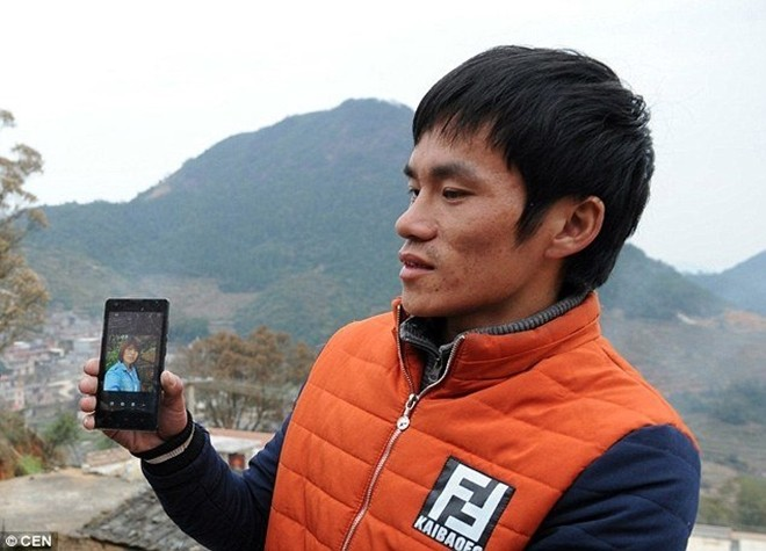 Một người đàn ông cho xem hình ảnh người vợ Việt Nam mà anh này đã phải trả tiền cho công ty môi giới để lấy được, nhưng nay cô ấy đã bỏ trốn. Ảnh: CEN