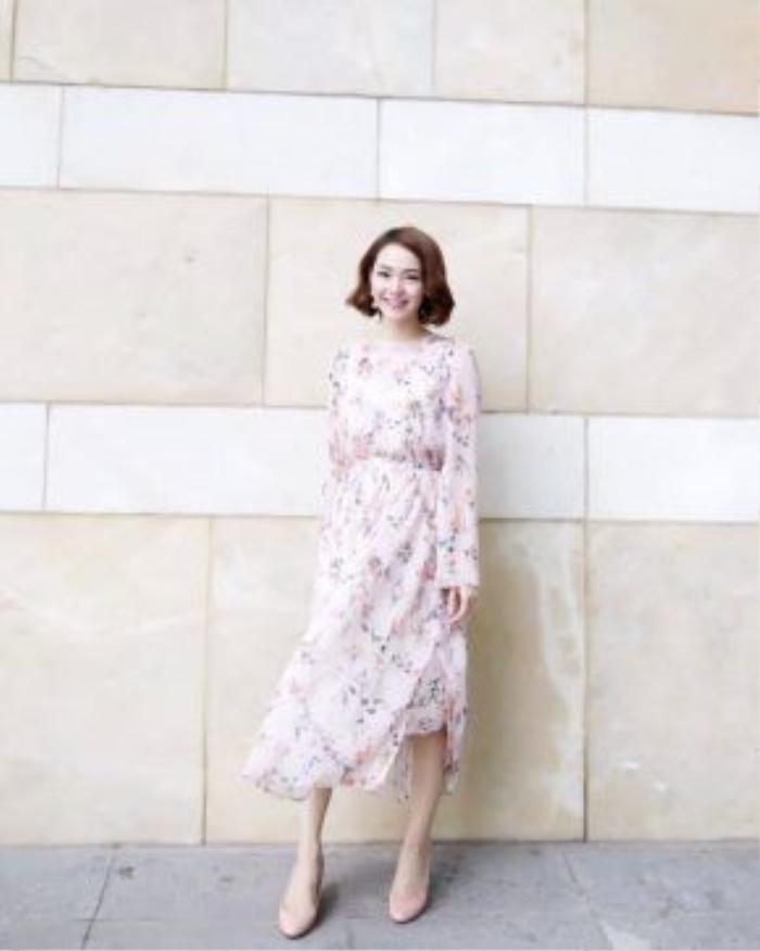 Đầm midi màu hồng pastel in họa tiết hoa cỏ khiến Minh Hằng trở nên vô cùng đài các và nền nã. Hãy chọn thêm một đôi sandal hoặc giày búp bê cùng tông để hoàn thiện set đồ ngọt ngào và nữ tính của bạn.