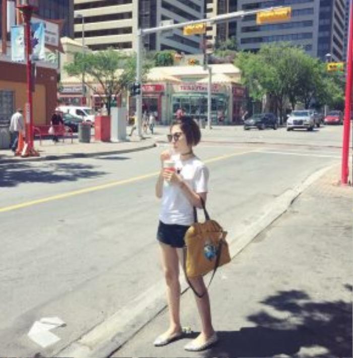 Yumi Dương năng động xuống phố cùng áo thun trắng, quần short jean, giày ballet và một chiếc túi xách với gam màu tươi tắn.