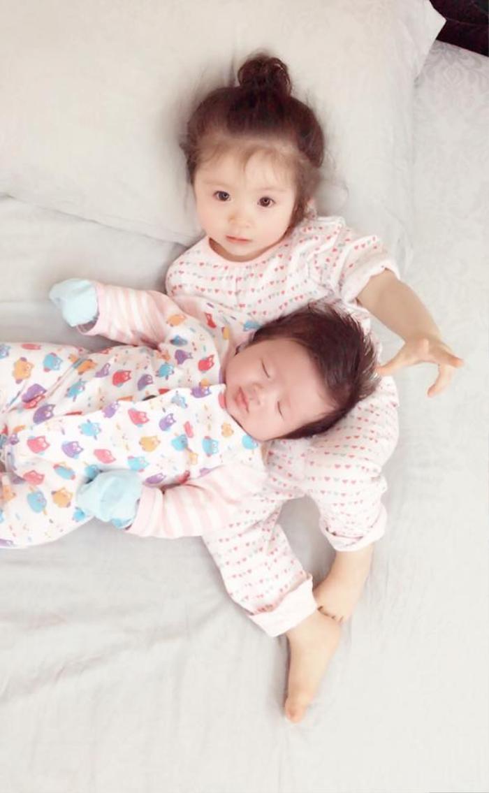 """Từ ngày lên chức chị gái, Cadie tỏ ra đảm đang trong việc trông em. """" ngủ luôn rồi nên dù mỏi lắm mình cũng hỏng dám nhúc nhích"""" - Elly Trần hóm hỉnh viết về con gái."""