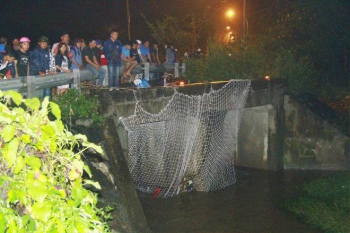 Lực lượng chức năng giăng lưới tại khu vực cống nước ngăn nạn nhân bị trôi - Ảnh: Xuân An