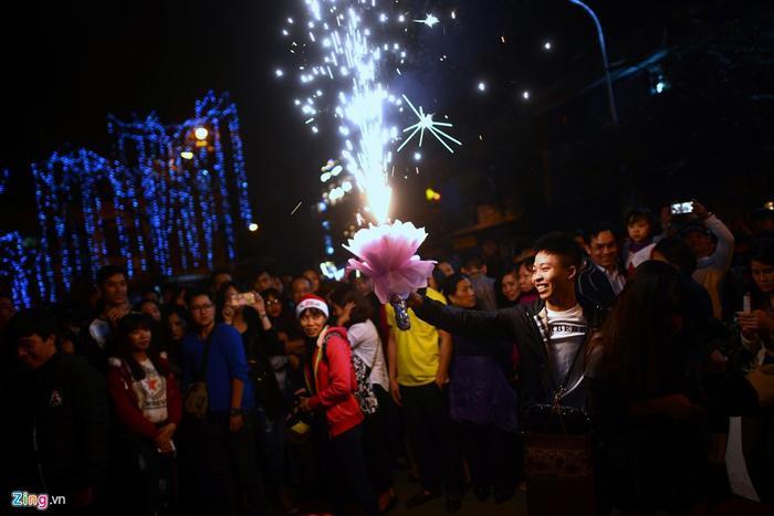 Tại thời khắc 0h, trước cửa Nhà thờ Lớn, người dân bất ngờ thấy một thanh niên rút bó hoa kèm theo cây pháo sáng.
