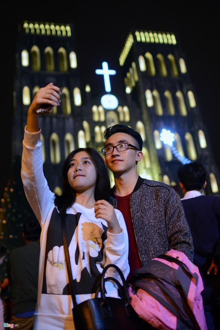 Đôi bạn trẻ khác giữ lại khoảnh khắc kỷ niệm, ý nghĩa đêm Giáng sinh.