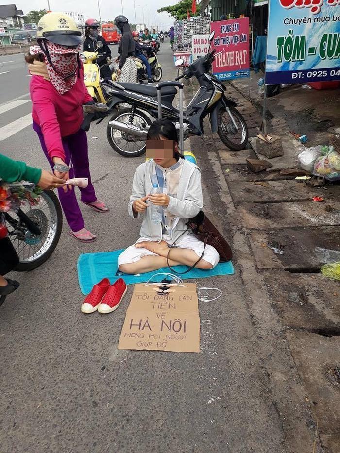 """Q.T ngồi xin tiền bên lề đường cùng với tấm bảng và dòng chữ """"Tôi đang cần tiền về Hà Nội, mong mọi người giúp đỡ."""""""